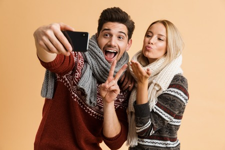 Portrait of a cheerful young couple dressed in sweaters and scarves standing together isolated over beige background, taking a selfie Stock Photo