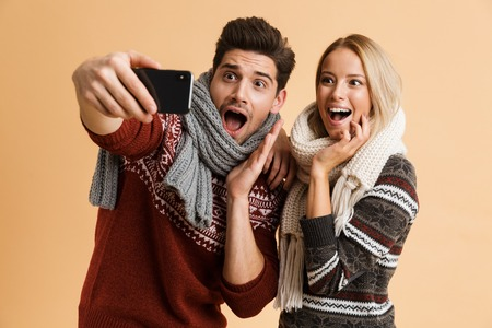 Portrait of an excited young couple dressed in sweaters and scarves standing together isolated over beige background, taking a selfie