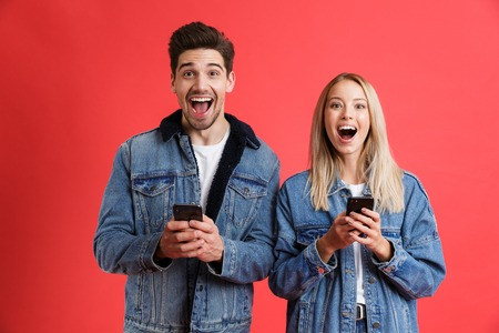 Portrait of an excited young couple dressed in denim jackets standing together isolated over red background, using mobile phones Imagens