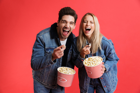 Portrait of a laughing young couple dressed in denim jackets standing together isolated over red background, watching movie, eating popcorn