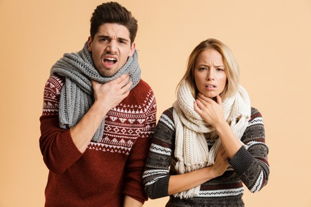 Portrait of a frozen young couple dressed in sweaters and scarves standing together isolated over beige background, shaking Фото со стока