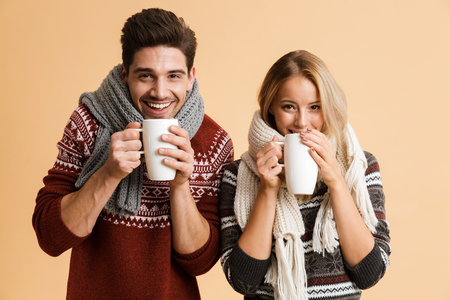 Portrait of a smiling young couple dressed in sweaters and scarves standing together isolated over beige background, holding cups with tea