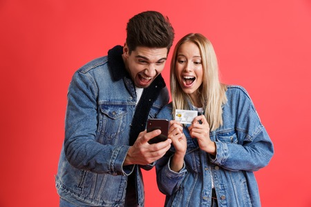 Portrait of a happy young couple dressed in denim jackets standing together isolated over red background, using mobile phone, holding credit card