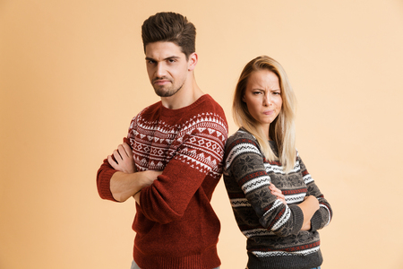 Portrait of an upset young couple dressed in sweaters standing together isolated over beige background, arms folded