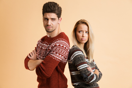Portrait of a disappointed young couple dressed in sweaters standing together isolated over beige background, arms folded