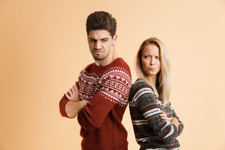 Portrait of an angry young couple dressed in sweaters standing together isolated over beige background, arms folded