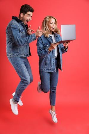 Retrato de cuerpo entero de una pareja joven emocionada vestida con chaquetas de mezclilla saltando juntos aislados sobre fondo rojo, mirando a la computadora portátil, señalar con el dedo