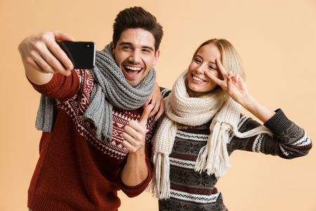 Portrait of a joyful young couple dressed in sweaters and scarves standing isolated over beige backgorund, taking a selfie together