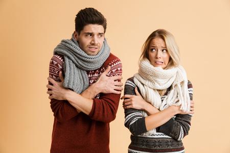 Retrato de una joven pareja congelada vestida con suéteres y bufandas de pie juntos aislados sobre fondo beige, temblando, mirando el uno al otro