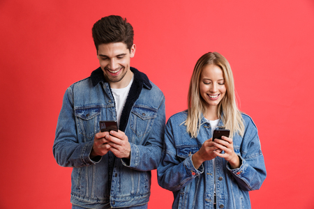 Portrait of a smiling young couple dressed in denim jackets standing together isolated over red background, using mobile phones Imagens