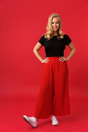 Full length portrait of joyous blond woman 20s smiling at camera while standing with arms on waist isolated over red background in studio