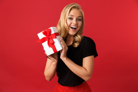 Portrait of an excited young woman isolated over red background, holding present box