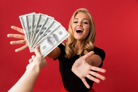 Image of young excited woman looking at money which someone gives to her isolated over red background.
