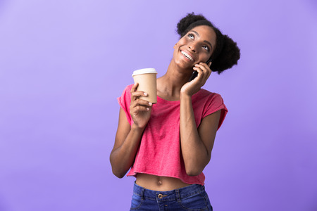 Candid african american woman in casual clothing holding paper cup with takeaway coffee while talking on smartphone isolated over violet background