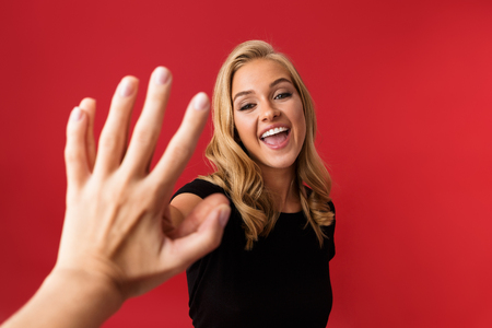 Image of young excited woman looking camera give a high five to someones hand isolated over red background.