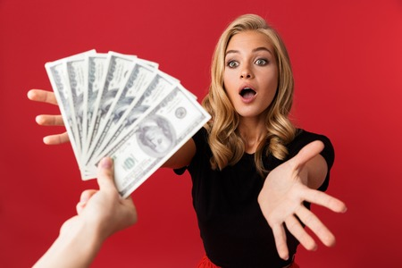 Image of young excited shocked woman looking at money which someone gives to her isolated over red background.