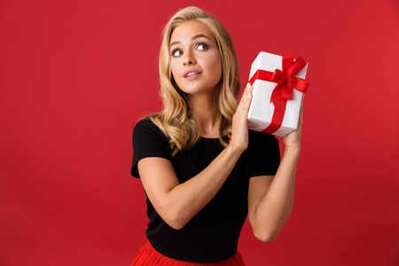 Portrait of a lovely young woman isolated over red background, holding present box Reklamní fotografie