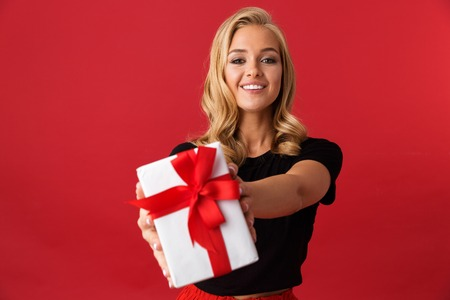 Portrait of a happy young woman isolated over red background, giving present box Reklamní fotografie