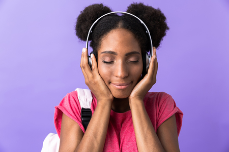 Photo of charming african american woman wearing backpack and white headphones listening to music isolated over violet background Stock Photo