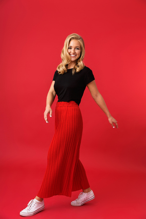 Full length portrait of cheerful blond woman 20s smiling and walking isolated over red background in studio