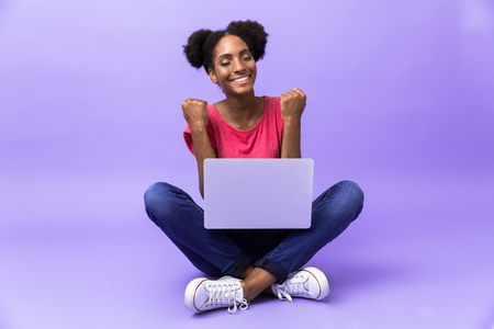 Photo of excited african american woman smiling and using silver laptop, while sitting on floor with legs crossed isolated over violet background