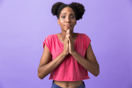 Photo of attractive african american woman keeping palms together for pray isolated over violet background