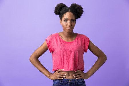 Photo of upset african american woman standing with hands on waist isolated over violet background Stock Photo