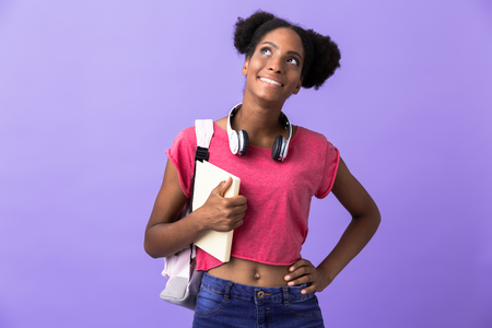 Photo of african american female student wearing backpack holding exercise book isolated over violet background