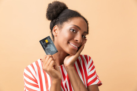 Joyous african american woman smiling and holding credit card isolated over beige background Stock Photo