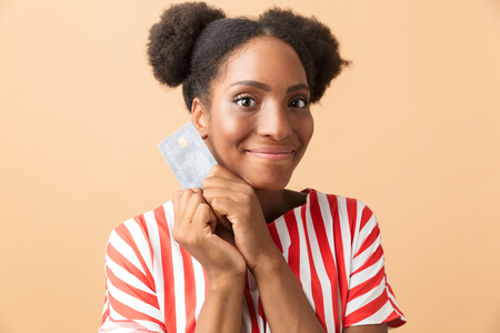 Positive african american woman smiling and holding credit card isolated over beige background 版權商用圖片