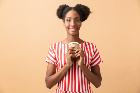 Happy african american woman in casual clothing holding paper cup with takeaway coffee isolated over beige background