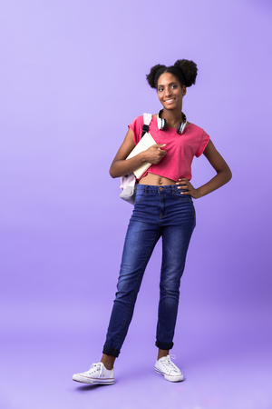 Full length photo of african american woman student wearing backpack holding exercise book isolated over violet background