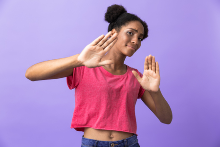 Photo of dissatisfied african american woman showing stop gesture with hands isolated over violet background