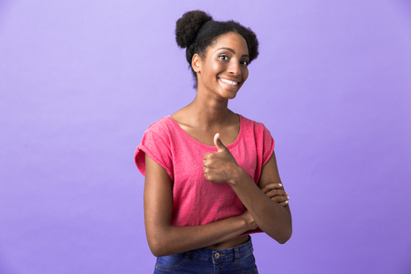 Photo of adorable african american woman with afro hairstyle showing thumb up isolated over violet background Imagens