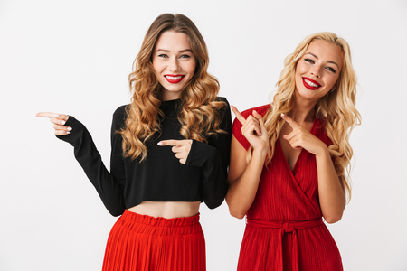 Image of emotional young two girls friends gossiping isolated over white wall dressed in black and red clothes pointing to copyspace.