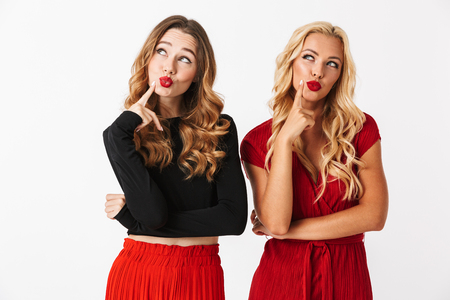 Portrait of two pensive young smartly dressed women wearing makeup standing isolated over white background, looking away Stock fotó