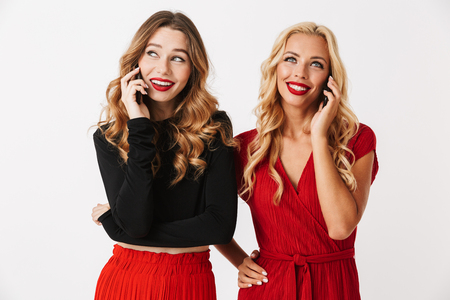 Portrait of two pretty young smartly dressed women wearing makeup standing isolated over white background,talking on mobile phones
