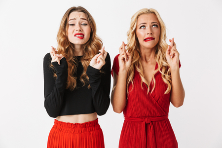 Image of nervous young two girls friends make hopeful gesture isolated over white wall dressed in black and red clothes. Stok Fotoğraf