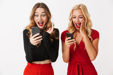 Portrait of two excited young smartly dressed women wearing makeup standing isolated over white background,using mobile phones, celebrating