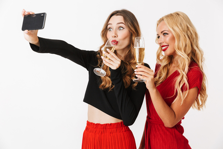 Portrait of two cheerful young smartly dressed women wearing makeup standing isolated over white background, taking a selfie, drinking champagne