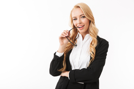 Foto van een Europese zakenvrouw die een kantoorpak draagt en een bril vasthoudt die op een witte achtergrond in de studio wordt geïsoleerd