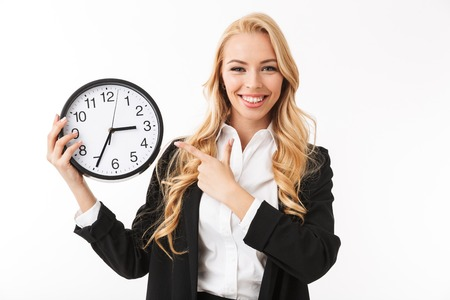 Portrait of a happy young businesswoman standing isolated over white background, showing clock, pointing finger