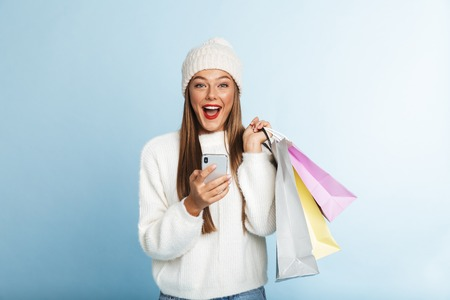 Cheerful young woman wearing sweater standing isolated over blue background, holding mobile phone, carrying shopping bags