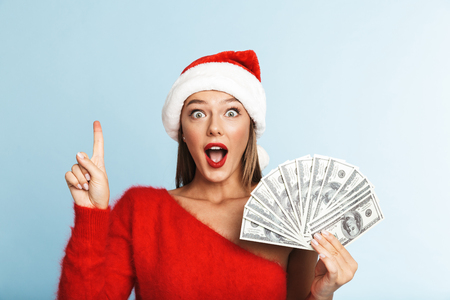 Cheerful young woman wearing santa claus hat standing isolated over blue background, showing money banknotes, pointing finger up