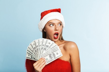 Image of a beautiful happy young woman wearing christmas hat posing isolated over blue wall background holding money.