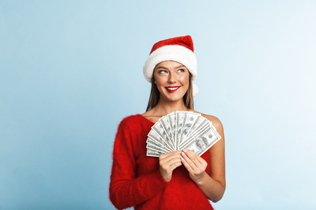 Cheerful young woman wearing santa claus hat standing isolated over blue background, showing money banknotes Stock Photo