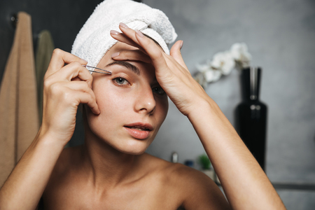 Pretty young woman with towel on head correcting eyebrows with tweezers in front of mirror in bathroom Stock Photo