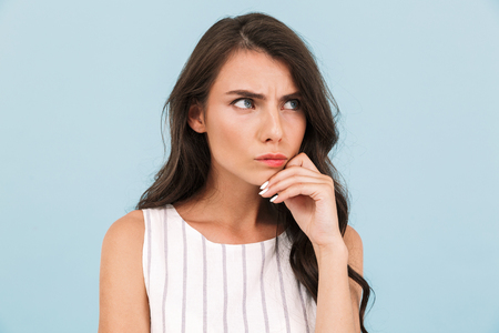 Image of emotional displeased young woman posing isolated over blue background wall.