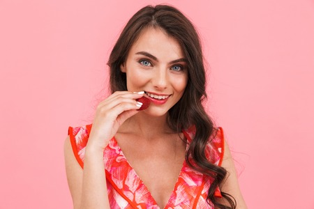 Image of a happy excited young woman posing isolated over pink background wall eat strawberry.