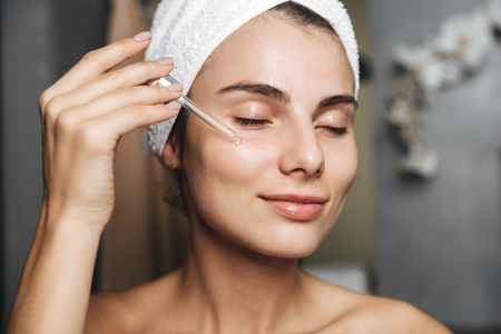 Photo of lovely woman with towel on head applying cosmetic oil on her face while standing in bathroom